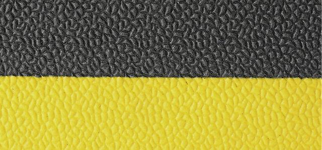 Egy fekete-sárga ipari szőnyeg struktúrája