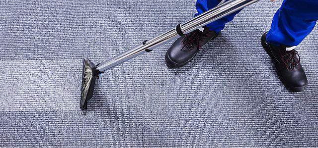 Jemand reinigt den Teppichboden